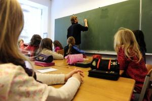 A teacher writes on the blackboard durin